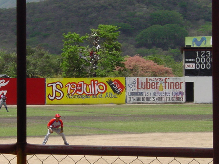 Professional baseball in Esteli. Each main city in Nicaragua has a team. Games are played Friday thru Sunday, with double headers on Sunday. The players have jobs during the week day! Notice the free seats in the outfield trees.
